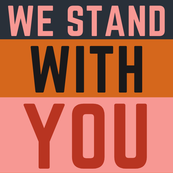 We Stand With You printed in capital letters on colored stripes